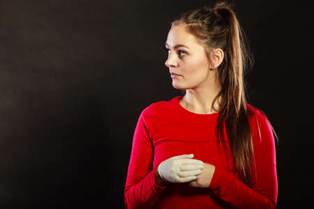 Portrait of pensive woman. in rubber glove. Attractive young girl thinking looking at blank copyspace in studio on black.