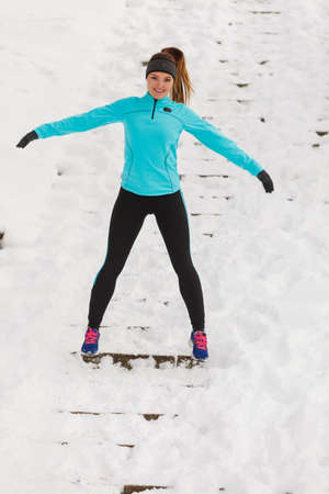 wintry weather: Winter holidays, spending leisure time outside. Young lady having fun on the snow. Girl is playing around, enjoying wintry weather in proper way.