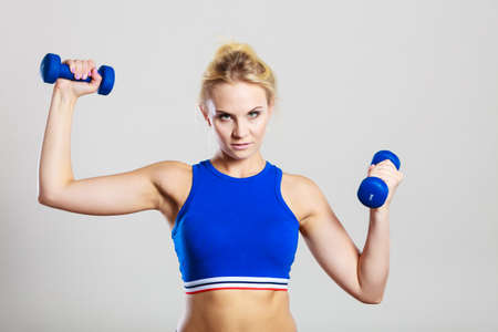 strong women: Sporty woman lifting light dumbbells weights. Fit girl exercising building muscles. Fitness and bodybuilding.