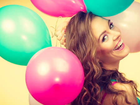 Joy and freedom. Lovely gorgeous smiling girl playing with colorful balloons. Young cute long hair woman have fun in summer time. Stock Photo
