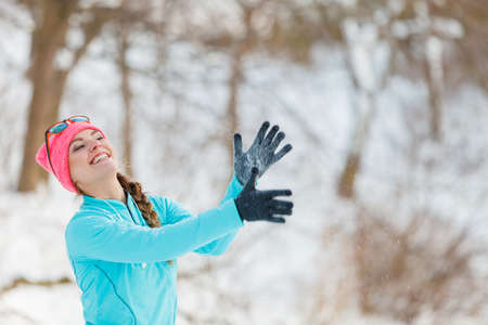 Girl having fun with snow in the park. Lady playing in winter season. Health nature entertainment fashion concept.