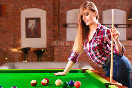 charming girl: Fashion and fun concept. Young charming girl posing by billiard pool. Attractive fashionable woman casual style spending time on recreation.