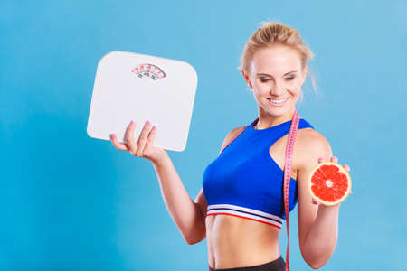 loosing: Loosing weight, diet and healthy nutrition. Fit fitness woman with measure tape holding weight scale in one and grapefruit in another hand, on blue