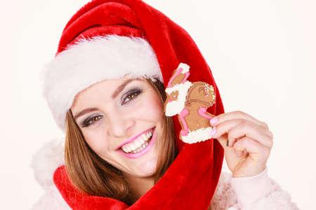 63737841 - Mujer que lleva el sombrero rojo que sostiene la galleta dulce  deliciosa de Navidad del pan de jengibre pequeño Papá Noel. a85f7660b57
