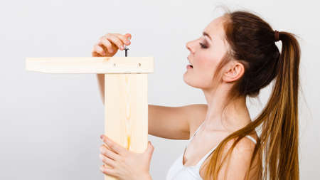 Woman assembling wooden furniture using hex key. DIY enthusiast. Young girl doing home improvement.