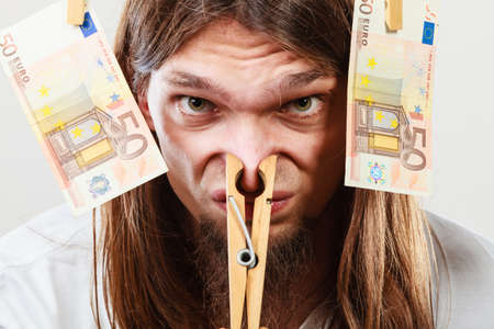 Money laundering concept. Young man with clothespin on his nose. Illegal business.