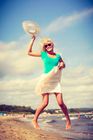 Summer time relax leisure concept. Attractive woman on the beach. Lady wearing sunglasses having fun playing with hat
