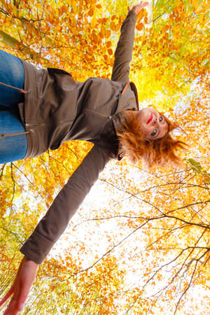 woodland scenery: Woodland scenery fun relax leisure outdoor concept. Lady dancing in forest. Redhead girl throwing herself into passionate dance in autumnal park.