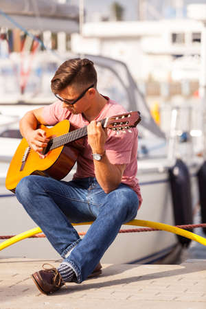 masculinity: Romance music sound talent masculinity concept. Young guitarist sitting on pier. Man playing on guitar in front of boat.