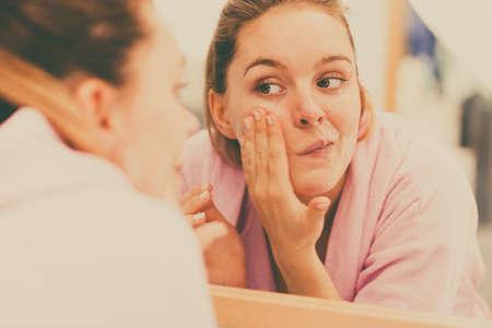 여자 스크럽 얼굴 마사지를하고, 화장실에서 그녀의 얼굴을 벗겨 청소. 소녀 피부 상태를 돌보는. 위생. 스킨 케어 스파 트리트먼트.