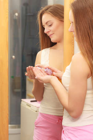 Woman in bathroom holding bottle with cosmetic oil. Girl taking care of her long smooth hair applying cream cosmetics. Haircare concept. Imagens