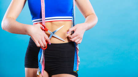 pinches: Weight gain diet liposuction concept. Woman with measure tapes pinches in the fat at the waist, holding scissors cut fold skin Stock Photo