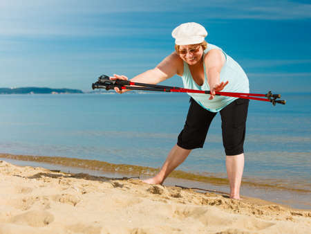 Senior woman enjoying nordic walking, doing warmup exercises with poles on sea shore, sunny summer day. Health, activity in old age.
