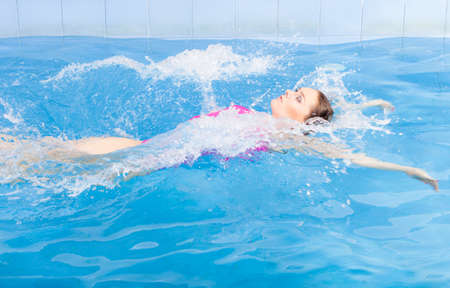 woman bath: Beautiful young woman in pink swimsuit swimming in blue pool on her back. Young female swimmer at holiday resort. Sport activity health concept. Stock Photo