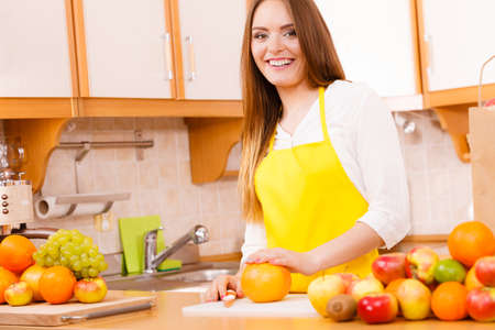 cook out: Health nature cuisine diet concept. Gorgeous cook preparing dish Younf girl wearing apron in kitchen making healthy food out of fruits.