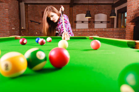 rivalry: Competition concept. Young focused girl having fun with billiard. Pretty fashionable woman spending time on playing rivalry. Stock Photo