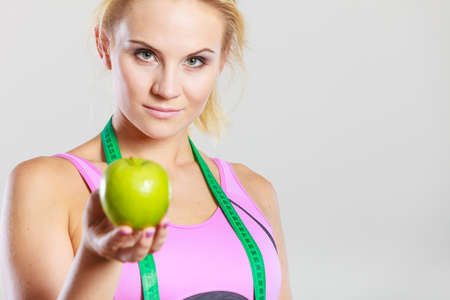 Time for diet slimming weight loss. Health care and healthy nutrition. Young fitness woman fit girl with measure tape and apple fruit on gray