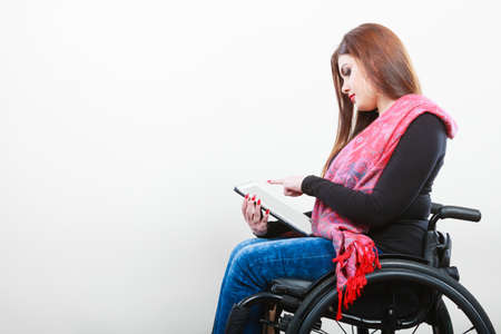 college life: College university and job concept. Mobile technology. Young student worker woman with tablet ebook on wheelchair. Disabled person in real life.