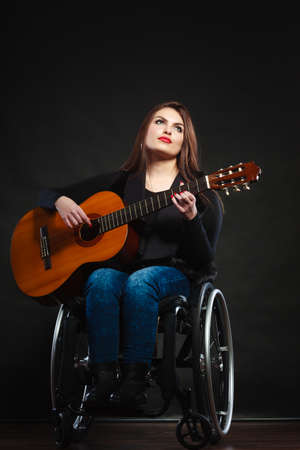 crippled: Disabled girl playing guitar. Young female musican on wheelchair. Hobby passion music relax concept.