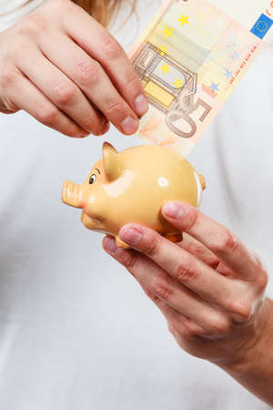 spending money: Spending money concept. Male hands with piggybank and euro banknote cash. Savings.
