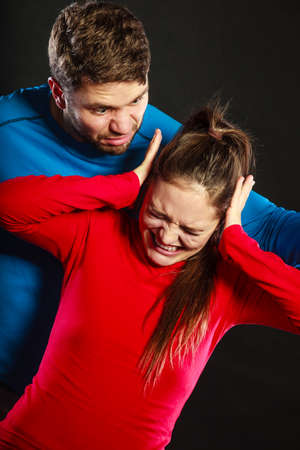 aggression: Husband abusing wife. Aggresive man screaming at crying scared woman. Domestic violence aggression.