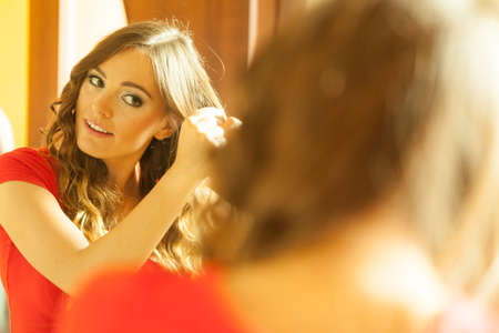 Hairstyles concept. Gorgeous woman with elegant make up making beauty hairdo curls on long straight dark hair. Reflection in mirror.