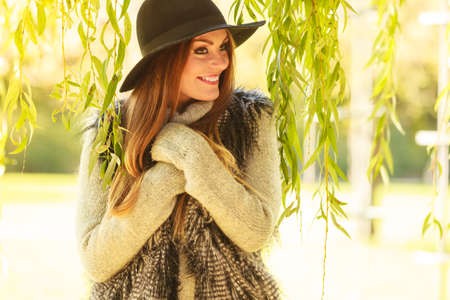 Autumnal female fashion. Pretty young woman wearing stylish sweater waistcoat and hat warm herself outdoor. Beauty fashionable woman standing in park around leaves of willow tree.