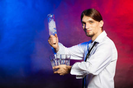 bartending: Alcohol liquor party relax flair bartending concept. Barman with bottle and glasses. Youthful tapster on colorful background.