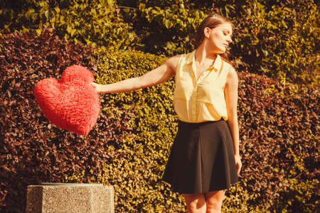 heartbreak: Love romance heartbreak sadness concept. Girl throwing heart into dumpster. Young lady holding plush love symbol over bin. Stock Photo