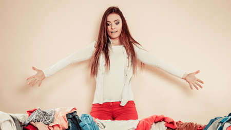 daily routine: Daily routine in household laundry clothing decision. Worried young woman with pile of colorful clothes on sofa. Stock Photo