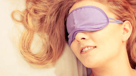 Tired woman sleeping in bed wearing blindfold sleep mask. Stock Photo