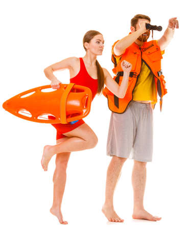 Lifeguards with rescue tube buoy and life vest jacket looking through binoculars. Man and woman supervising swimming pool running. Accident prevention.