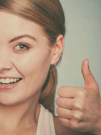 nonverbal communication: Expressing satisfaction with hand gesture. Nonverbal communication. Young girl smiling with thumbs up. Stock Photo