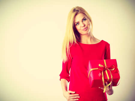 occasion: Occasions gifts people concept. Beautiful woman with red gift. Young blonde lady wearing nice outfit, dress. Present has the same colour.