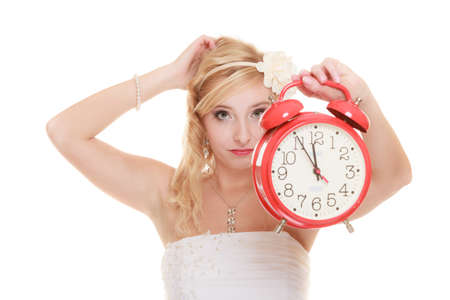 vestidos de epoca: Concepto de la boda. Tiempo para casarse. novia indeciso infeliz con el reloj de alarma roja. Hermosa mujer rubia de espera para el novio o la toma de decisiones aislado en blanco Foto de archivo