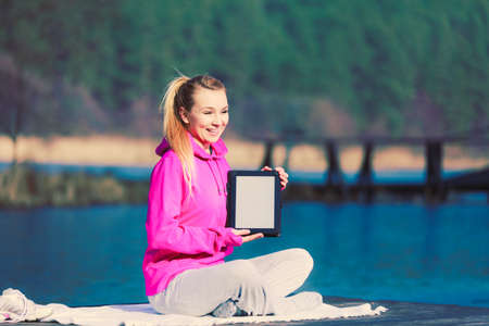 Young girl sitting in park learning yoga from tablet display screen. Taking care about healthy lifestyle and slim figure. Sport with technology.