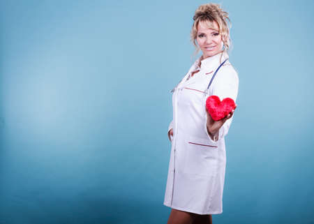 proffesional occupation: Help people concept. Medical idea of helping. Mature blonde happy doctor cardiologist with red heart enjoy her work. Middle aged woman wearing medic apron.