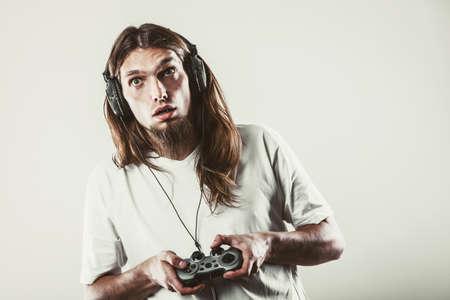 jugando videojuegos: concepto efectos de adicción. hombre deprimido infeliz joven con la almohadilla de joystick juegos de juego. Hombre adicto a la consola de videojuegos PlayStation.
