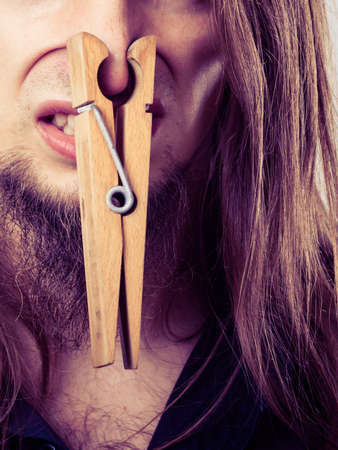 clogged: Unpleasant bad smell concept. Portrait of young long haired man with clogged nose by big clothespin.