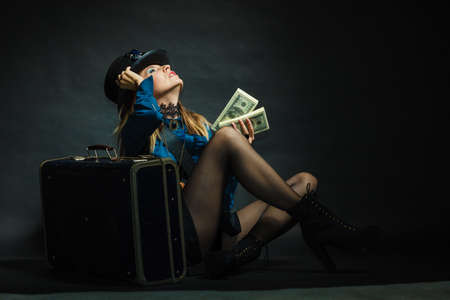 blunderbuss: Fashionable subculture weapon concept. Steampunk girl with cash. Young gorgeous lady in victorian fashion lying on floor with banknotes briefcase and blunderbuss. Stock Photo
