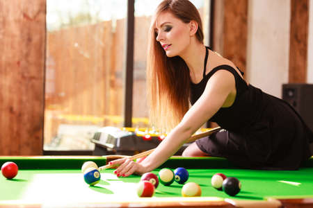 cue sticks: Competition concept. Young focused girl having fun with billiard. Pretty fashionable woman spending time on playing rivalry. Stock Photo