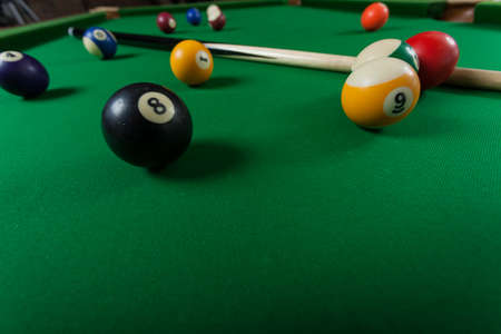 cue: Billiard balls and cue stick on green table. Pool game Stock Photo