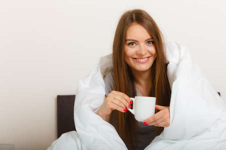 awaking: Bed relax sleep dream breakfast concept. Cheerful girl drinking coffee. Young lady having morning cup of hot beverage in bed.