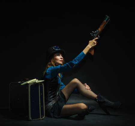 Subculture fashionable victorian elegant weapon concept. Steampunk girl armed and dangerous. Lady dressed in victorian fashion holding antique firearm aiming. Stock Photo
