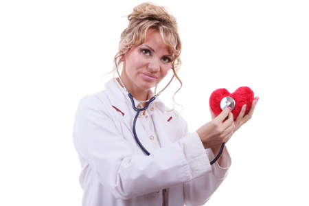 md: Medical examination of cardiology. Middle aged cardiologist with heart and stethoscope. Female doctor in white uniform makes measurement heartbeat. Isolated on white. Stock Photo