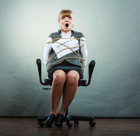 Afraid businesswoman bound by contract terms and conditions. Screaming scared woman tied to chair becoming slave. Business and law concept. Stock Photo
