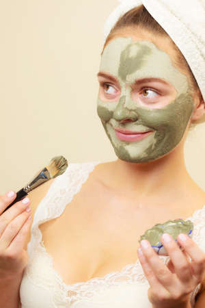mud girl: Skin care. Woman applying with brush clay mud mask to her face. Girl taking care of oily complexion. Beauty treatment.