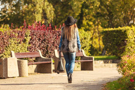 Female fashion. Back view of attractive long haired model wearing stylish clothes in park. Fashionable young model spending time on air.