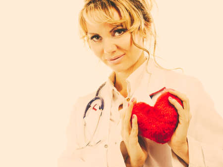 Periodic examinations. Cardiology concept. Female cardiologist holding red heart. Middle aged doctor with stethoscope and white medical apron uniform. Filtered.