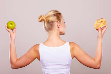 chose: Woman back view holds in hand cake sweet bun and apple fruit choosing, trying to resist temptation, make the right dietary choice. Weight loss diet dilemma concept. Stock Photo
